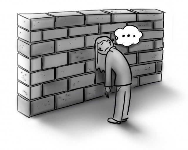 bored person standing in front of a brick wall